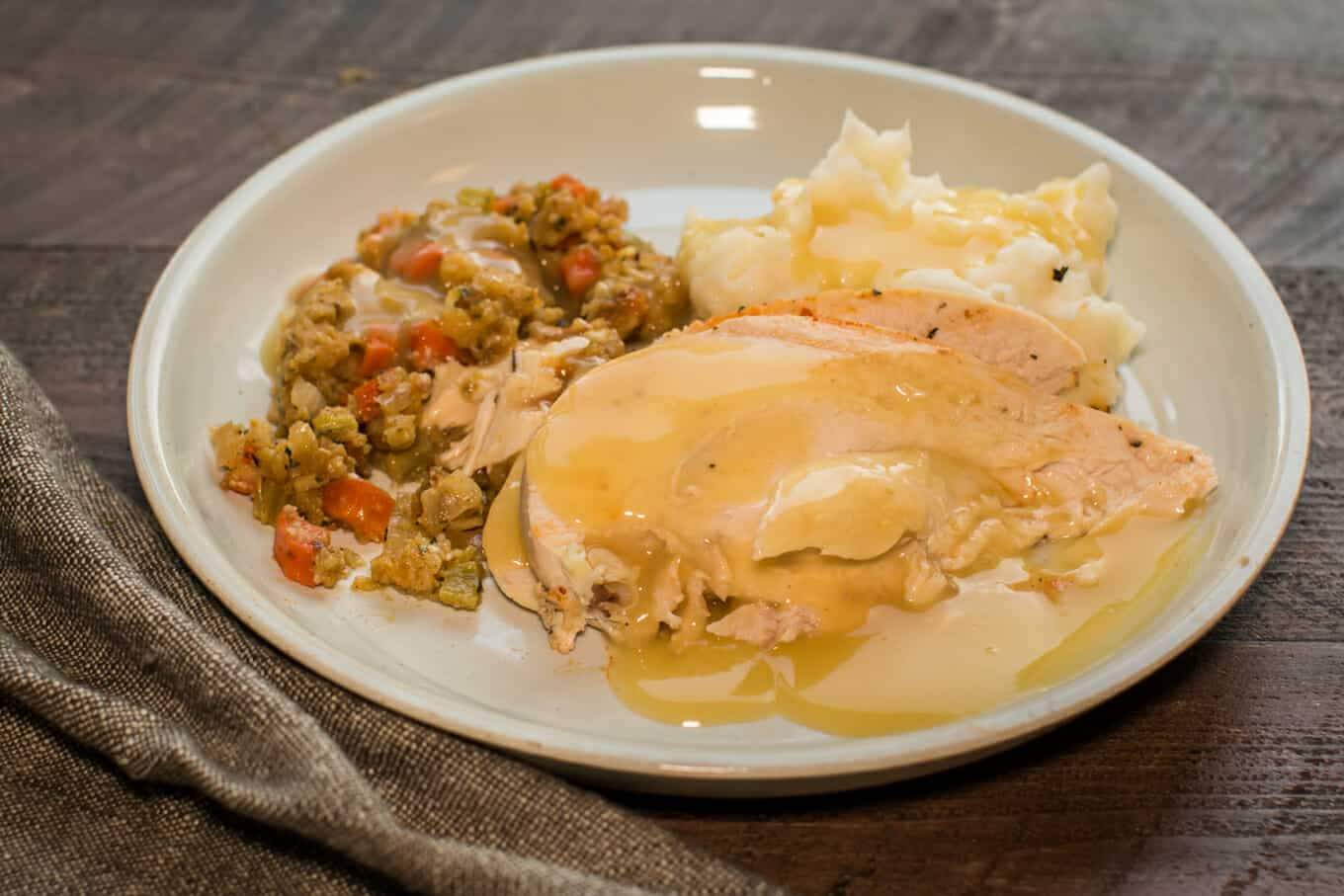sliced chicken with stuffing and mashed potatoes on a grey plate.