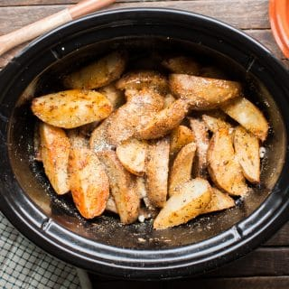 Potato wedges in slow cooker cooked with parmesan cheese and cajun seasonings.