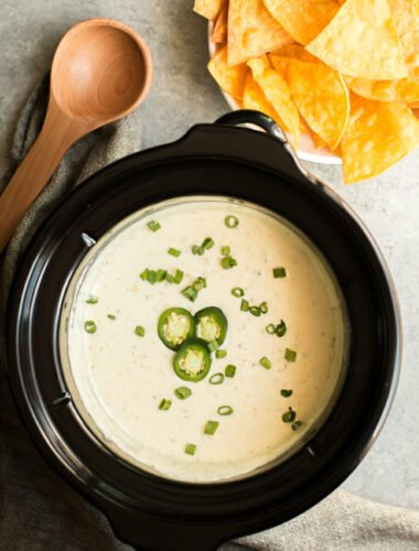 queso verde in slow cooker with chips on the side.