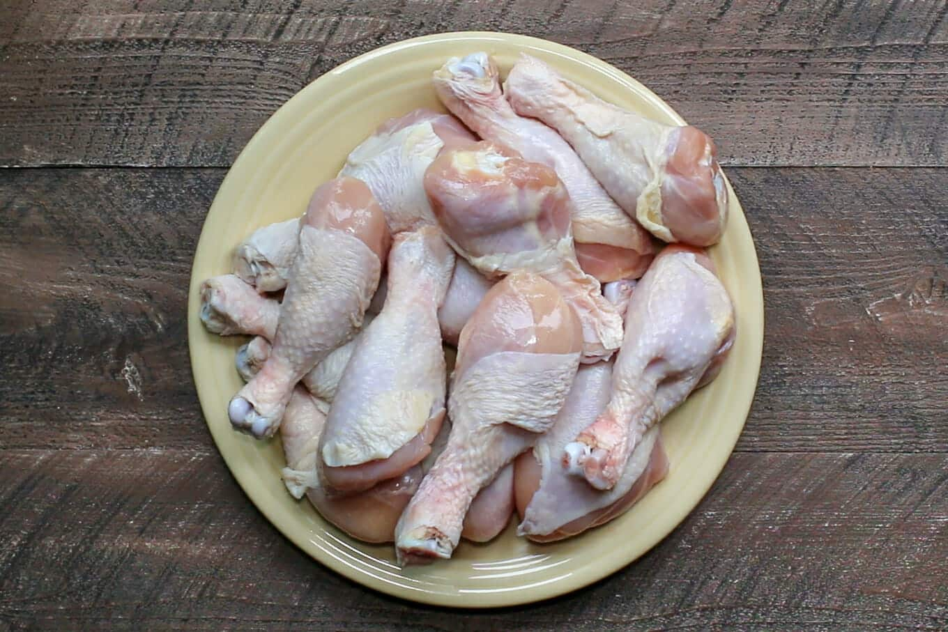 raw drumsticks on a yellow plate