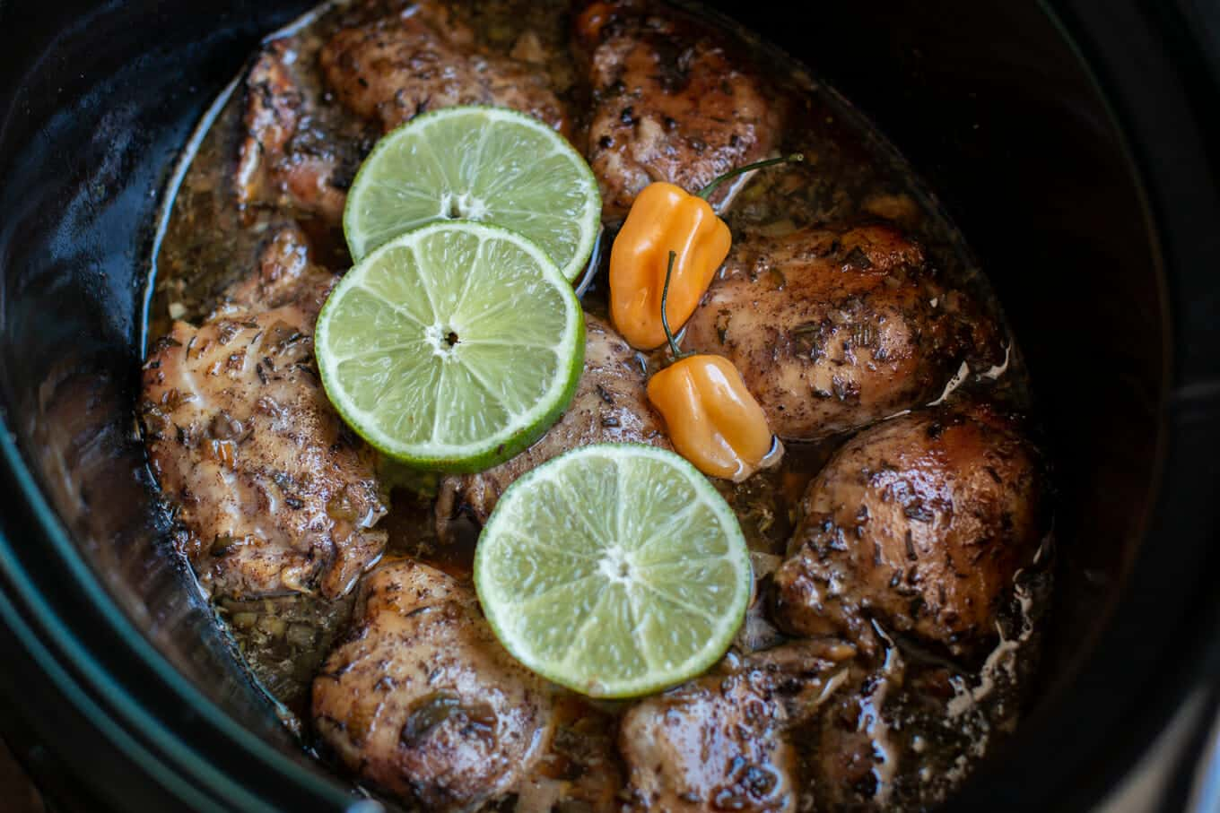 close up of Jamaican jerk chicken in slow cooker with limes and habaneros on top