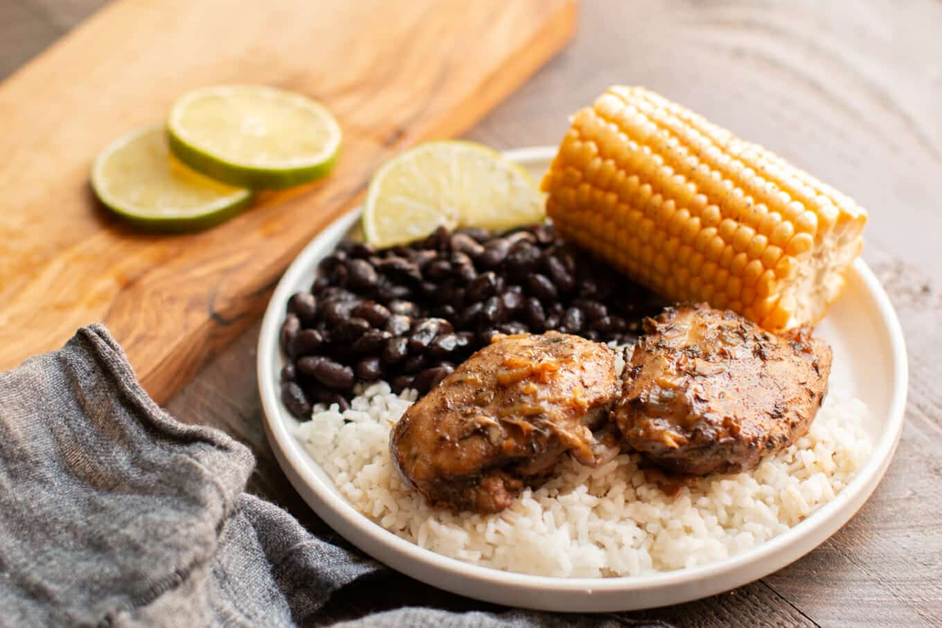 2 chicken thighs on rice with black beans and corm on white plate.