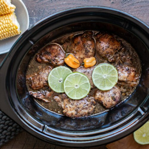 Jamaican jerk chicken in a slow cooker with limes and habanero on top.