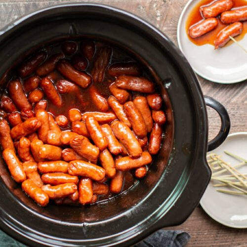 round slow cooker with little smokie wieners in it. Barbecue based sauce.