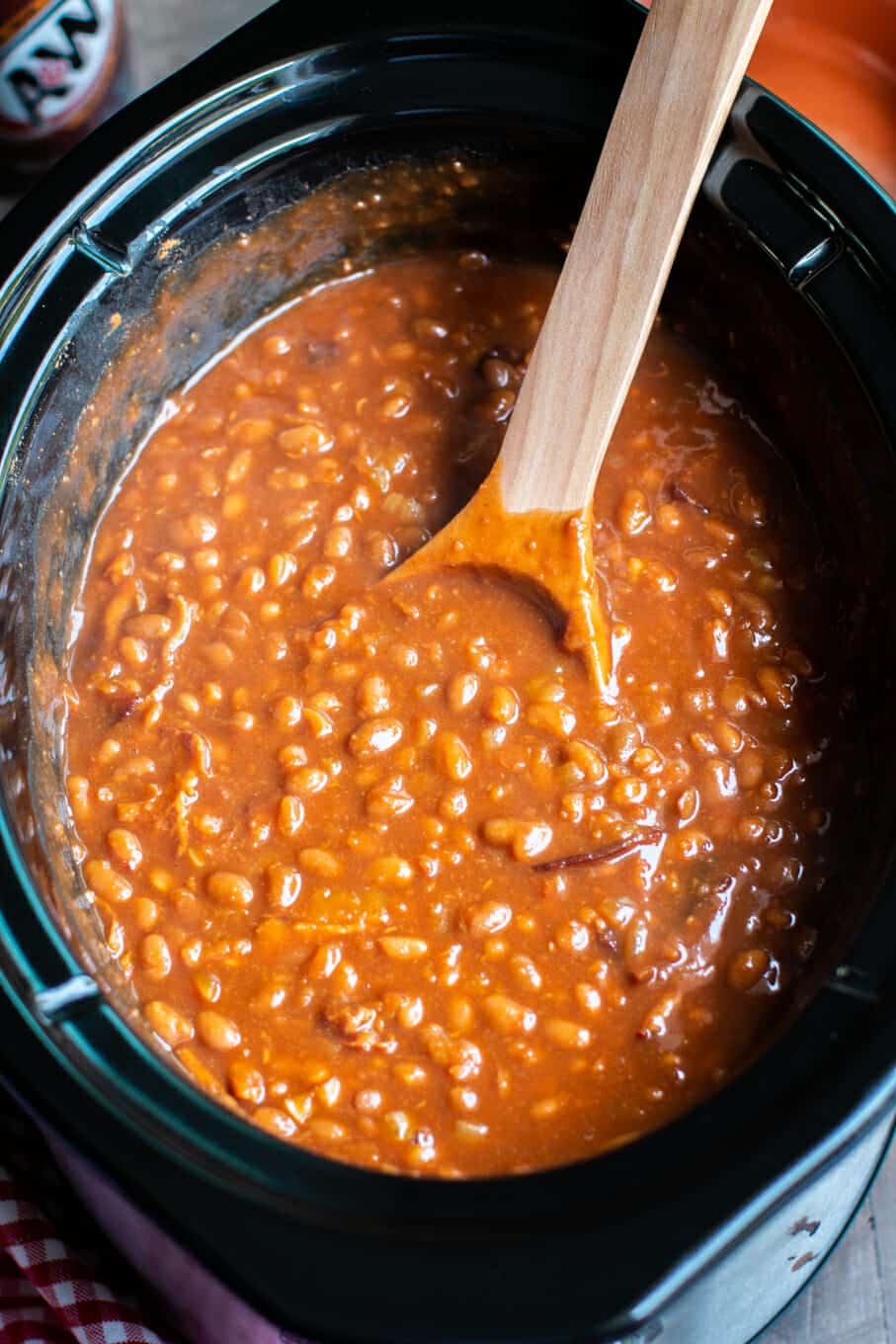 close up of root beer baked beans with wooden ladle in slow cooker