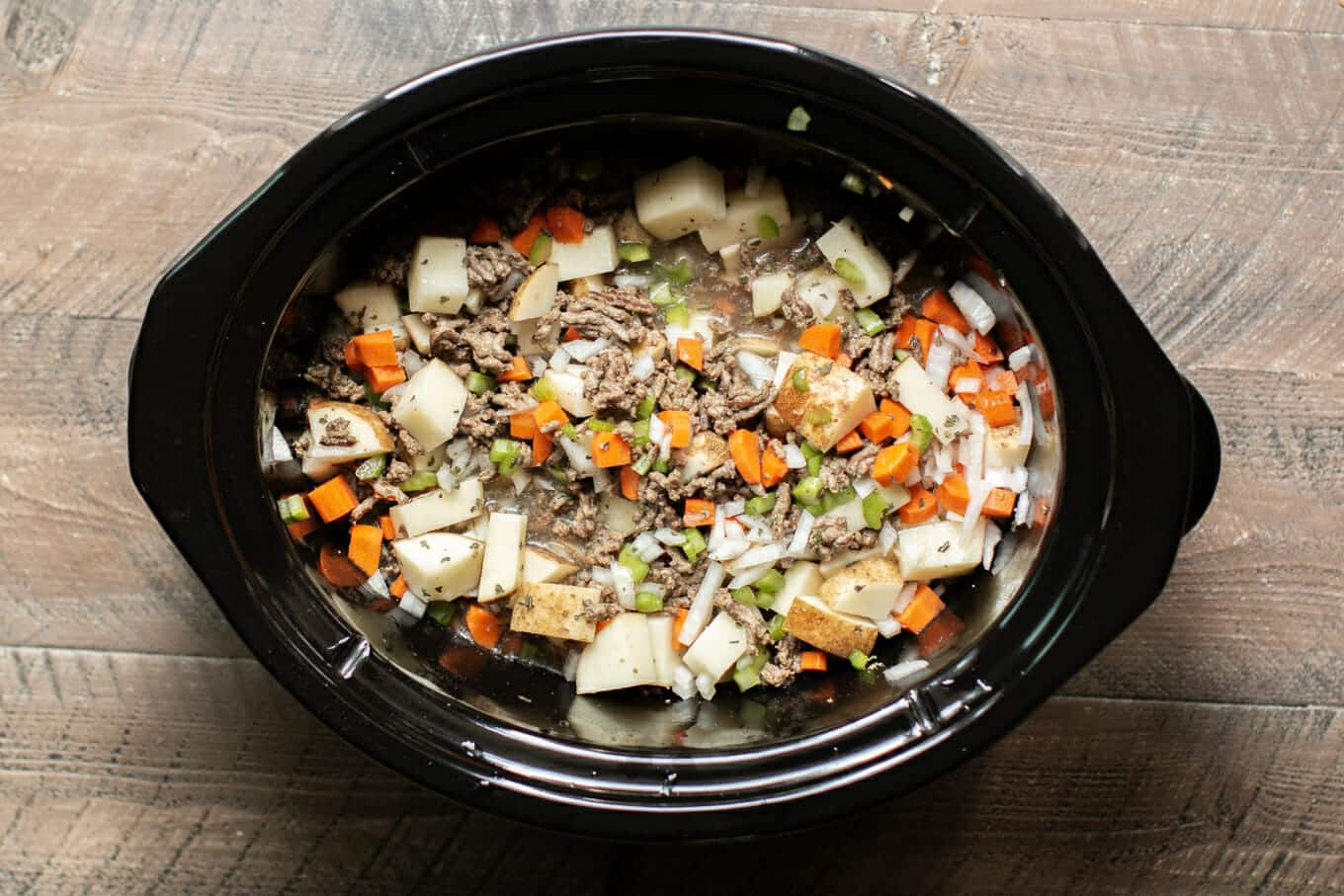 potatoes, hamburger, carrots, celery and chicken broth in a slow cooker.