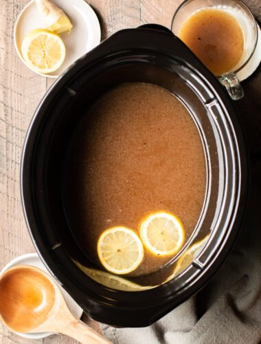 beef bone broth in the slow cooker with 2 lemon slices floating on top.