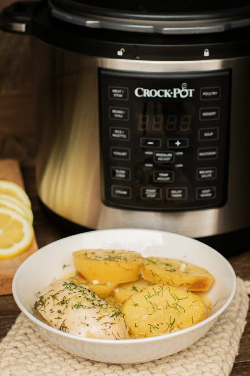 bowl of lemon chicken and potatoes in front of a pressure cooker.