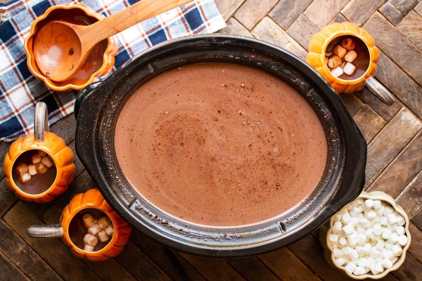 rich and creamy hot chocolate in slow cooker with pumpkin mugs around it.