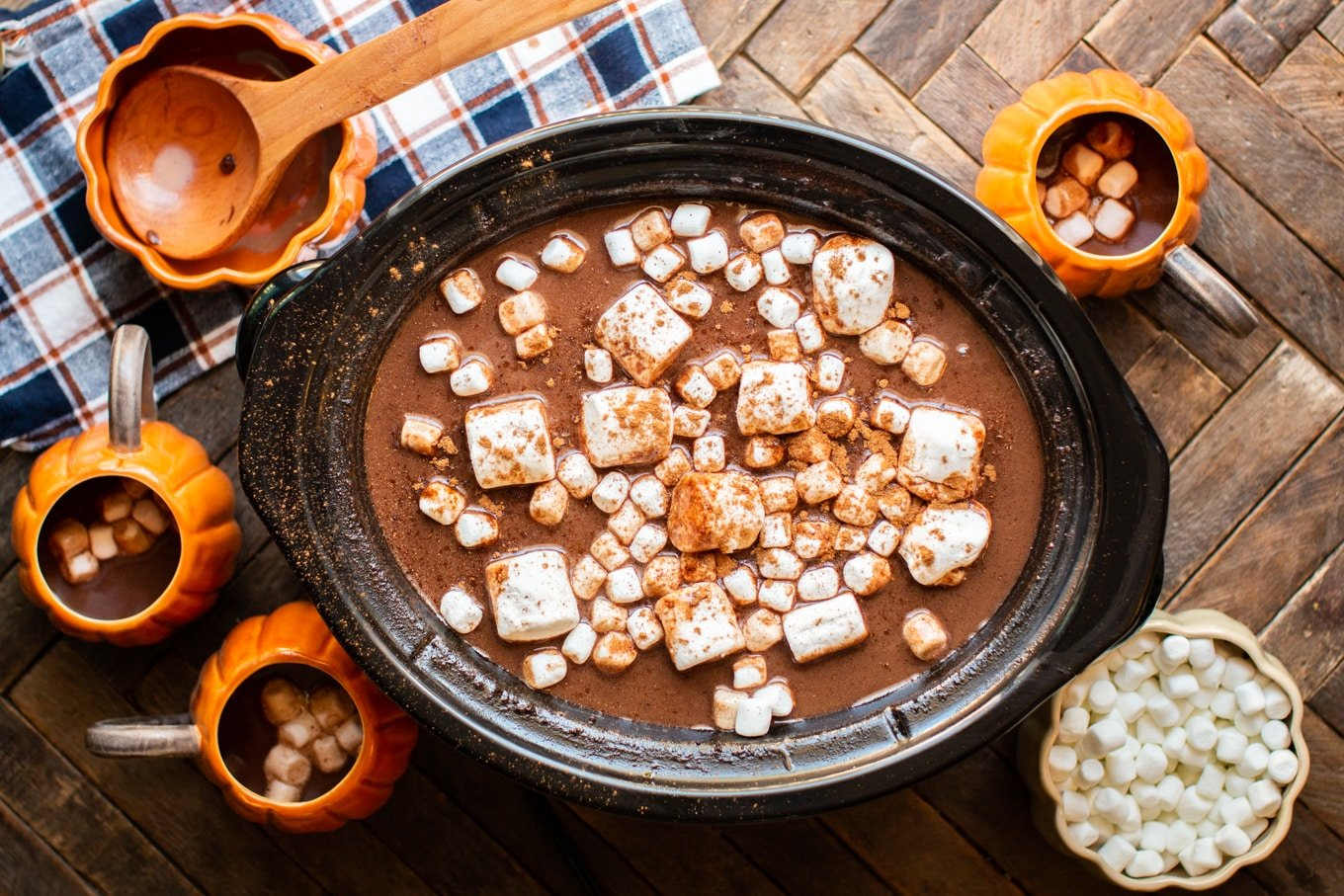 large and small marshmallows in pumpkin hot chocolate in a slow cooker.