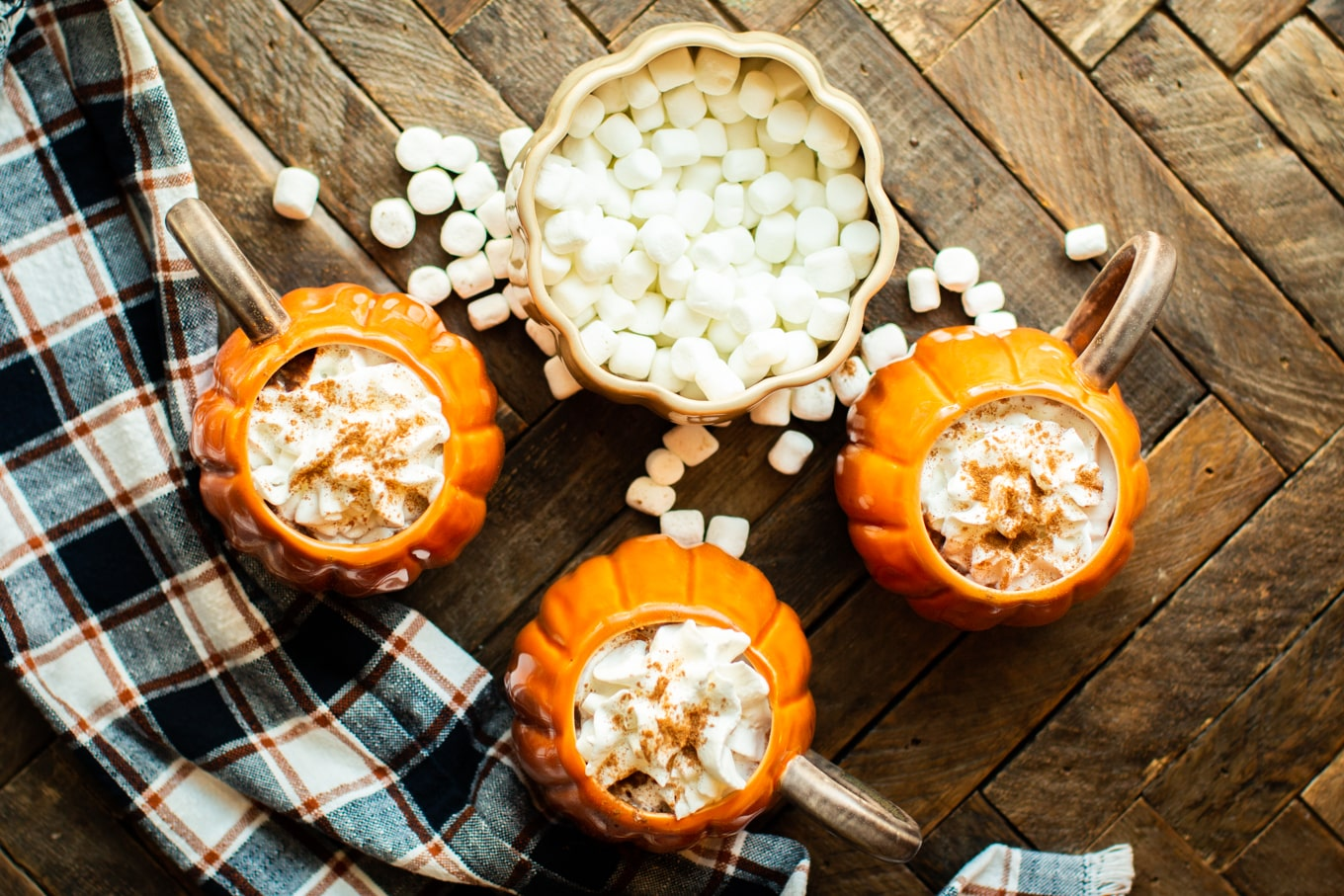 3 pumpkin mugs with whipped cream and nutmeg on top.