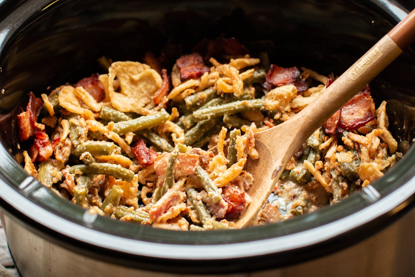 close up of green bean casserole with wooden spoon in it.