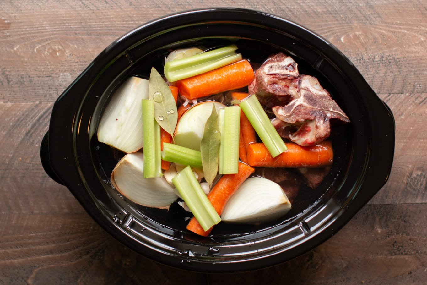 browned beef bones, onion, carrots, celery, onions and bay leaves in a slow cooker.