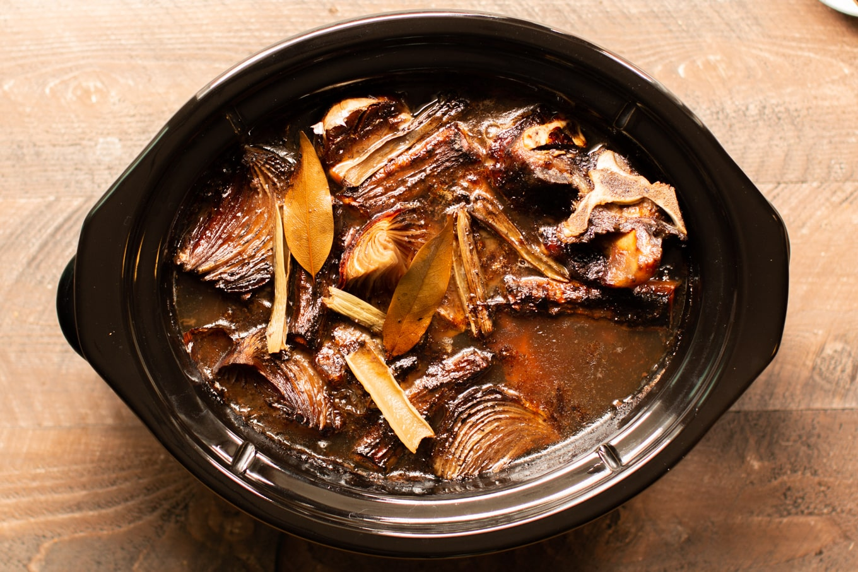 cooked beef bones and veggies in a slow cooker.