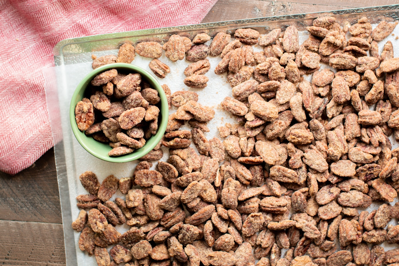 pecans on a wax paper-lined sheet tray. Some pecans in a small green bowl.