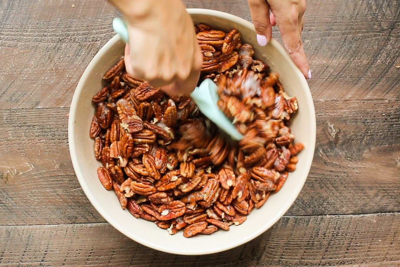 pecans being stirred with a green spatula.
