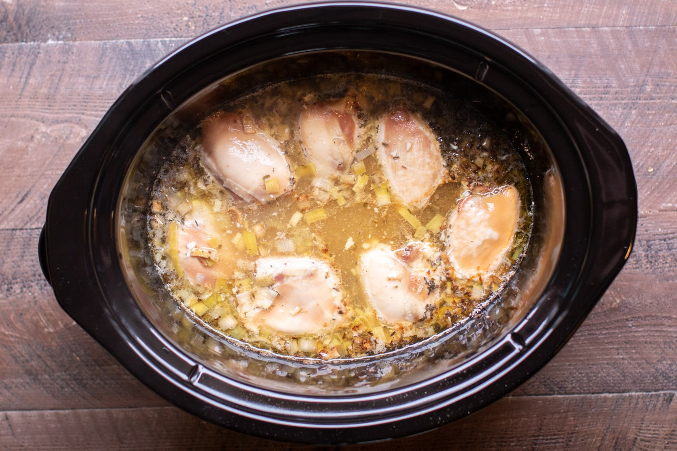 cooked chicken thighs in broth in a slow cooker.