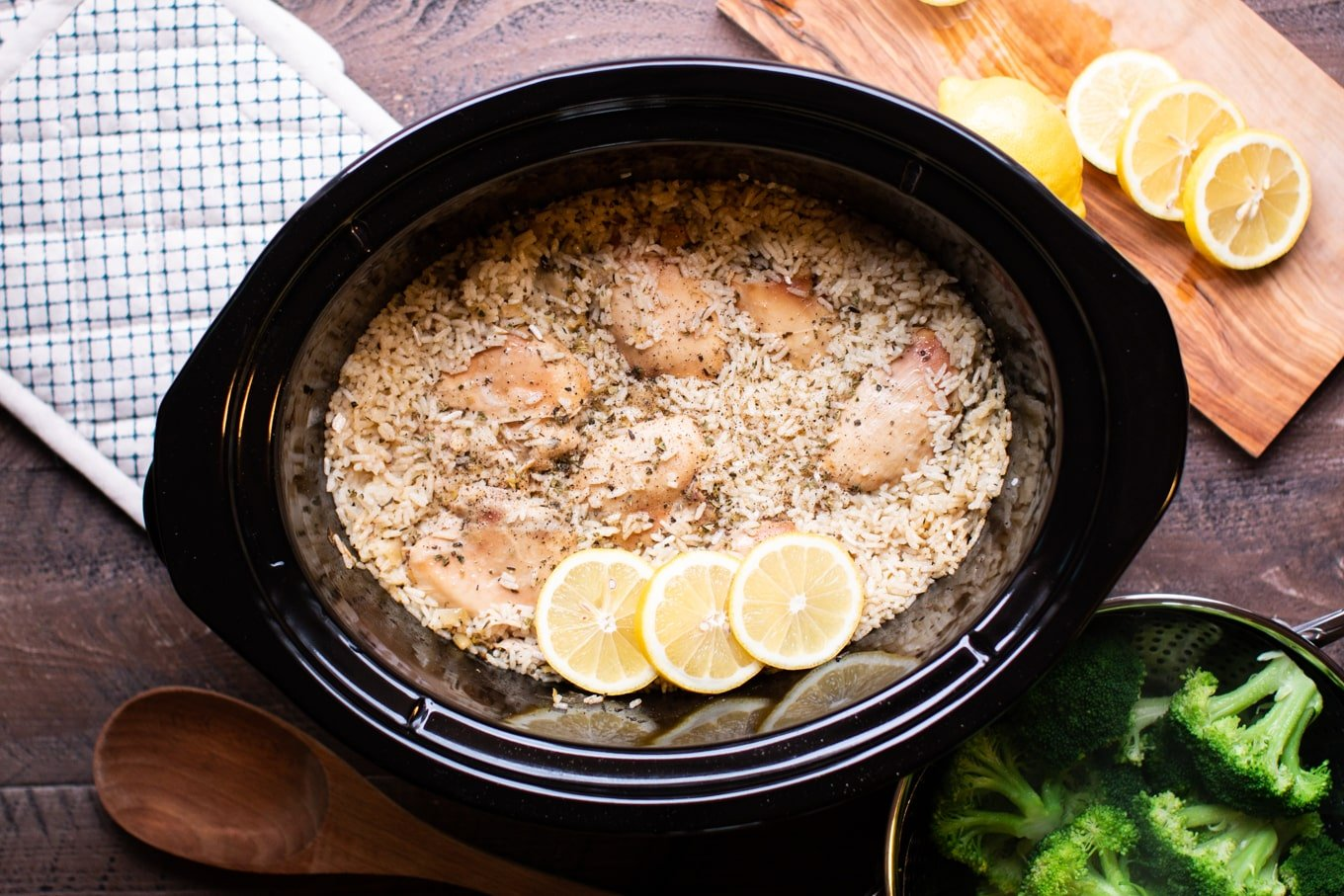 cooked lemon chicken and rice in slow cooker with wooden spoon on the side.