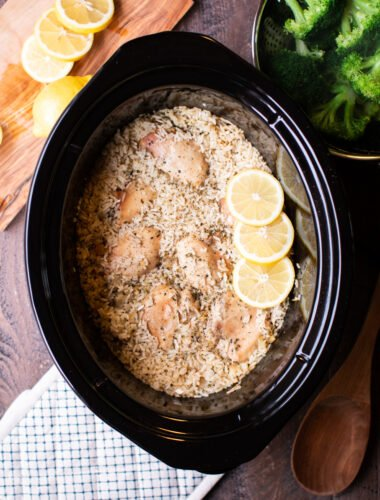 cooked rice and lemon chicken in a slow cooker with broccoli on the side.