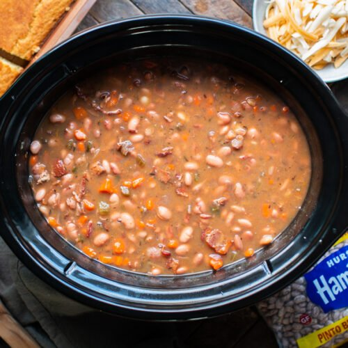 pinto beans cooked in slow cooker with cheese and cornbread on the side.