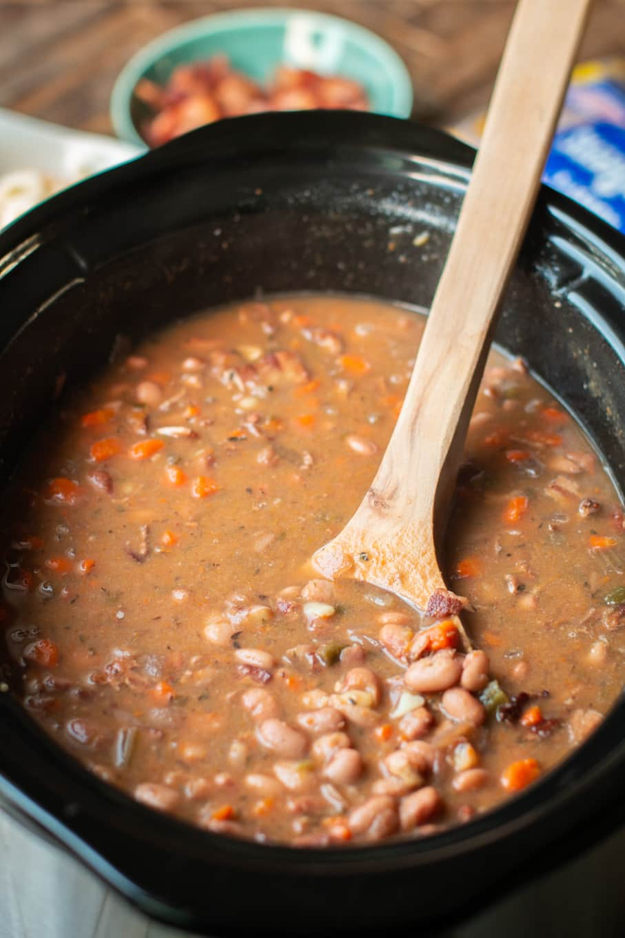 close up of pinto beans and bacon in a slow cooker.