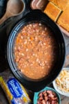 cooked pinto beans with carrots and bacon in a slow cooker.