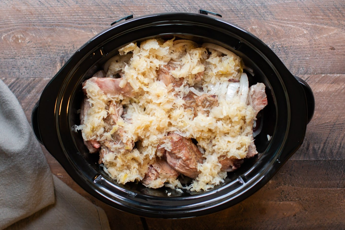 browned ribs, sauerkraut, potatoes, onion not yet cooked in a slow cooker.