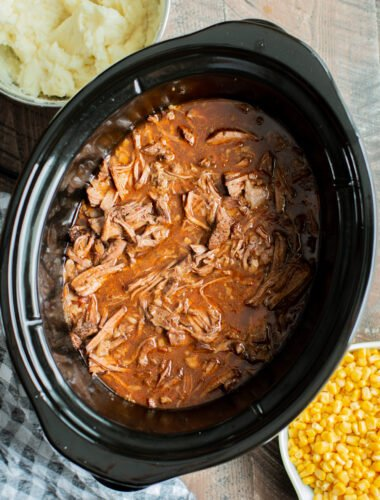 cooked shredded meat in a slow cooker in beef, onion and ketchup sauce.