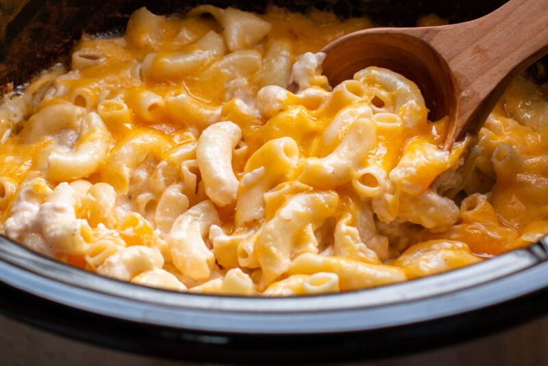 close up of cooked macaroni and cheese in a slow cooker with spoon in it.