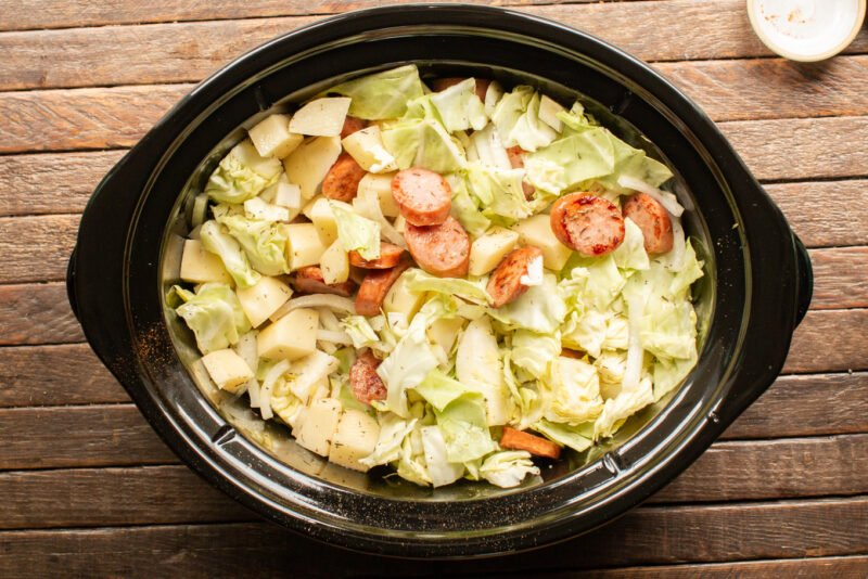 cabbage, potatoes, onions and kielbasa mixed together in a slow cooker.