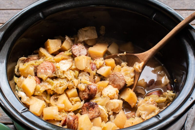 close up of potato, kielbasa, cabbage meal with a wooden spoon in it.