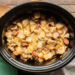 finished cooking potatoes, kielbasa and cabbage in an oval slow cooker.