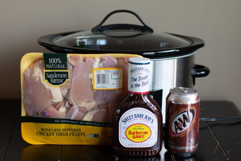Package of chicken thighs, root beer, barbecue sauce in front of slow cooker.