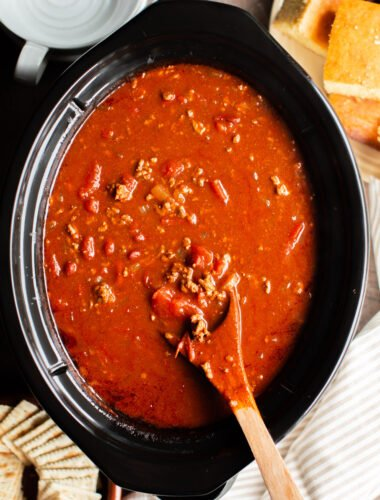 v8 chili in a slow cooker with a wooden spoon in it.