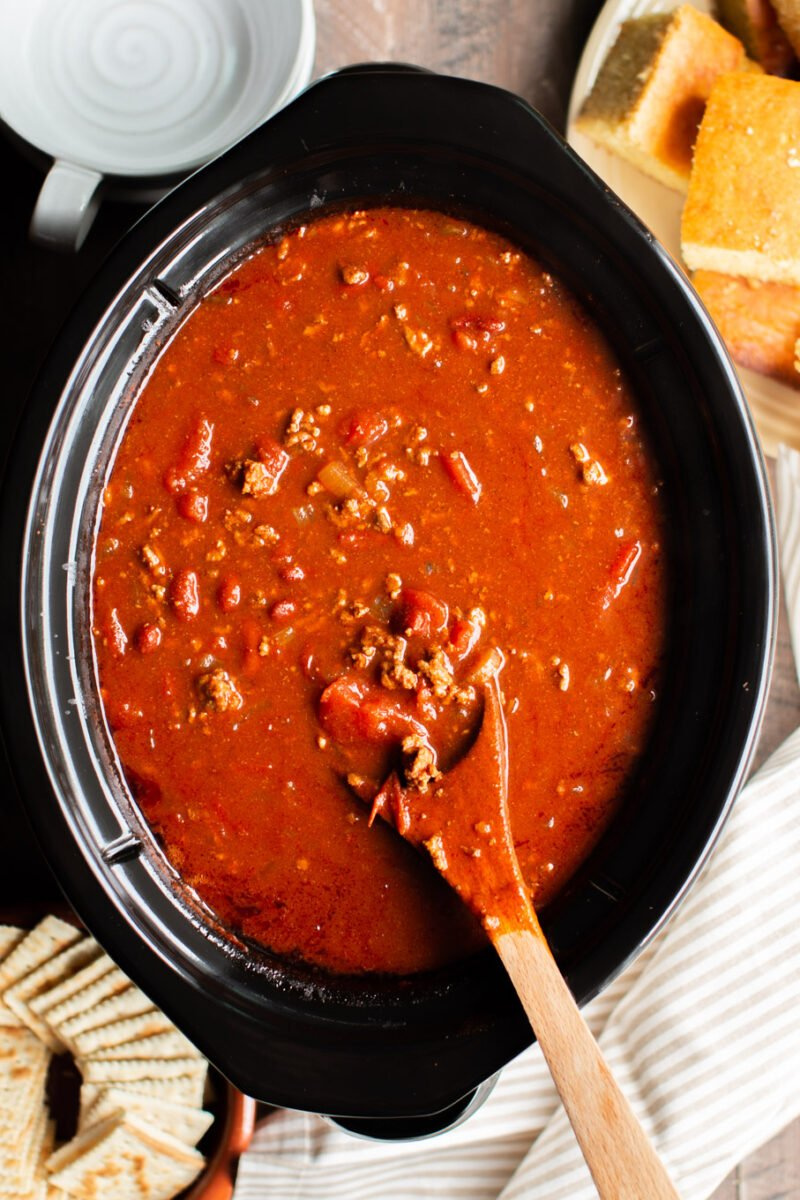 v8 chili in an oval slow cooker with cornbread on the side.