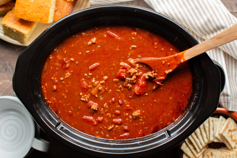 finished cooking v8 chili in a slow cooker with wooden ladle in it.