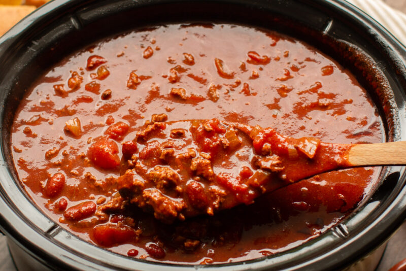 close up of v8 chili on a wooden spoon.