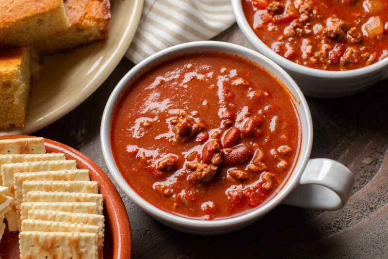 bowl of chili with cornbread on the side.