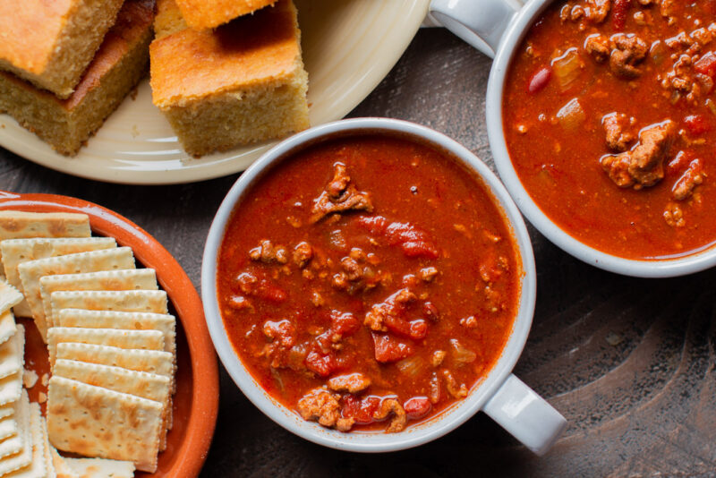 2 bowls of chili with crackers and cornbread on the side.