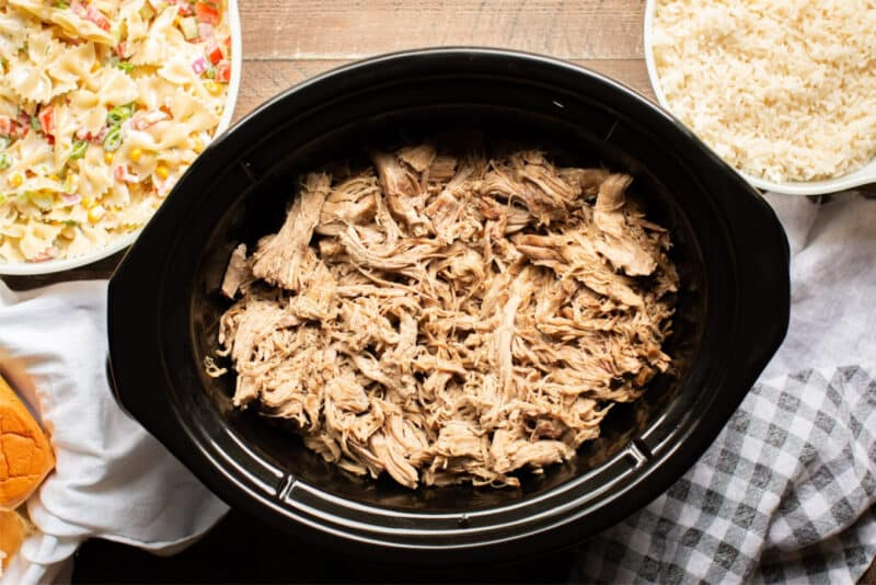 shredded kalua pig in crock pot with sides around it.