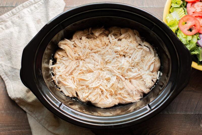 Slow cooker half full of white meat shredded chicken.
