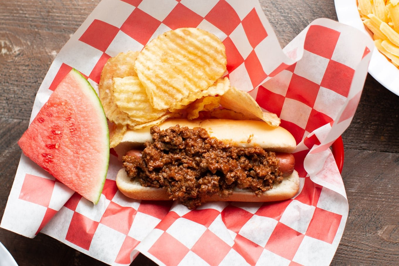 hot dog with chili on top on red and white checkered paper