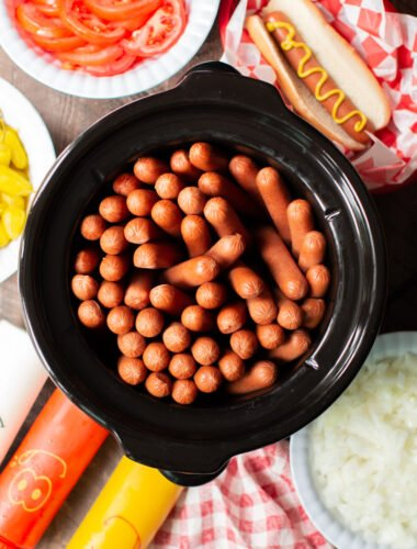slow cooker full of hot dogs with condiments on the side.