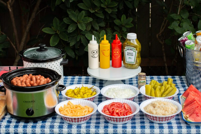 a hotdog bar with 2 slow cookers, bowls full of peppers, cheese, tomatoes, sauerkraut, pickles and onions.