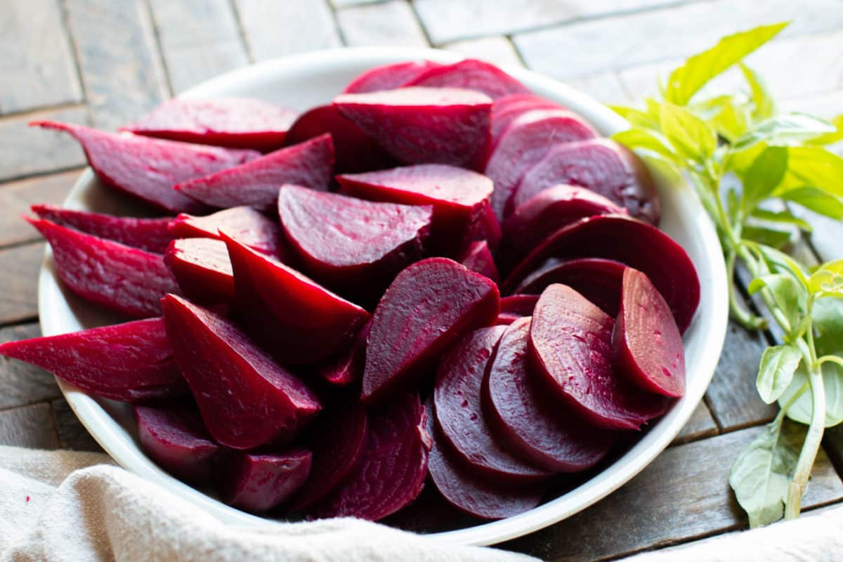 sliced beets on a plate with basil on the side.