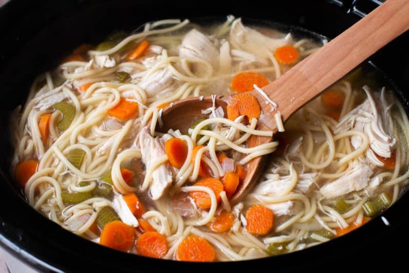 close up of cooked chicken noodle soup in a slow cooker.