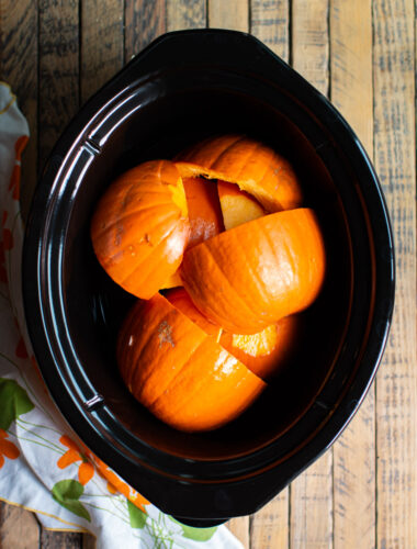cut up pieces of pumpkin in a slow cooker.