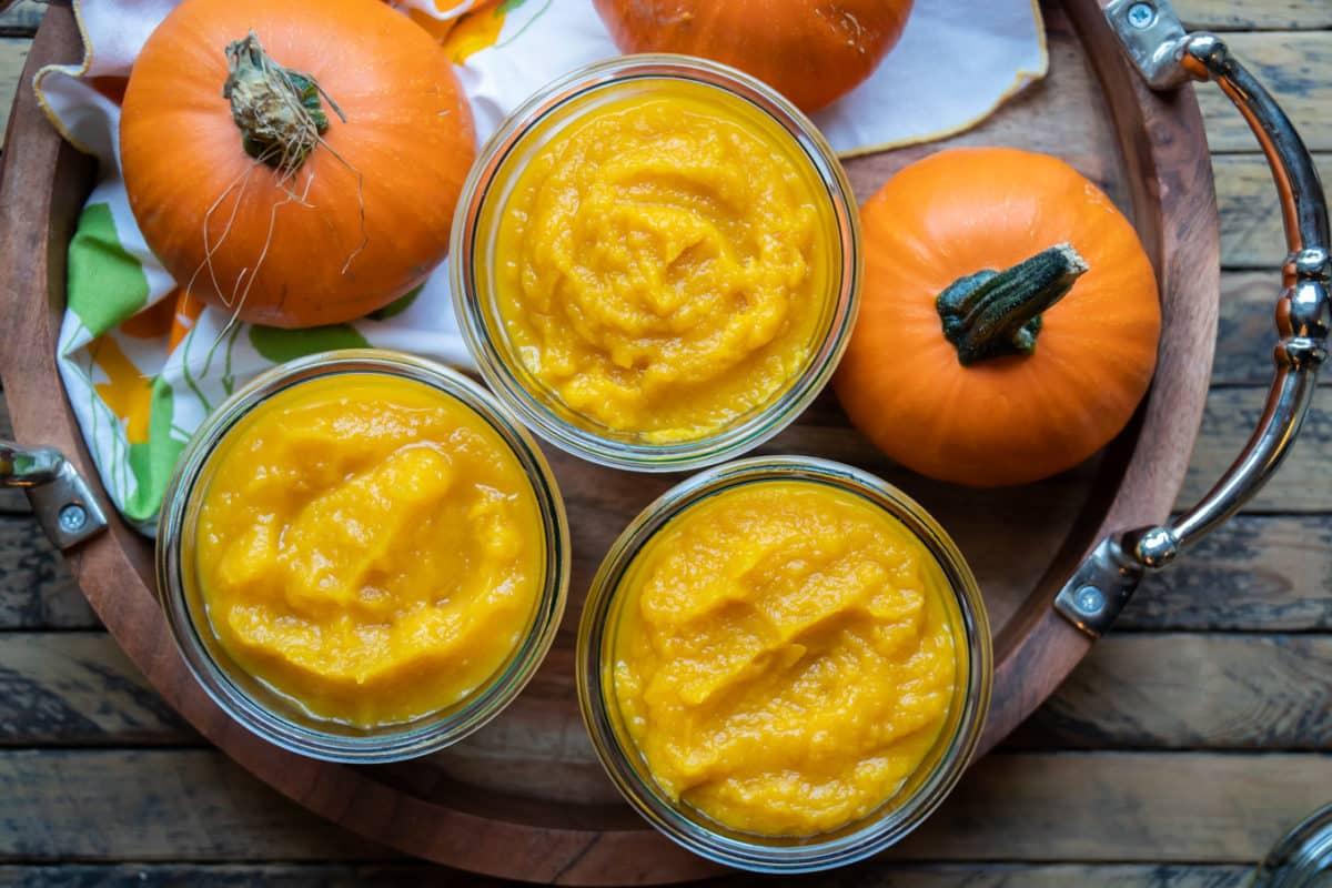 3 glass jars of pumpkin puree. 2 mini pumpkins next to them.