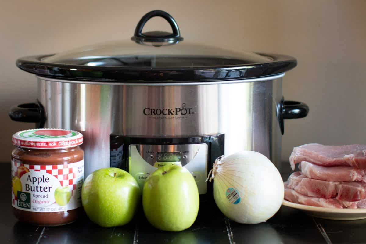 pork chops, apple butter, apples, white onion in front of a slow cooker.