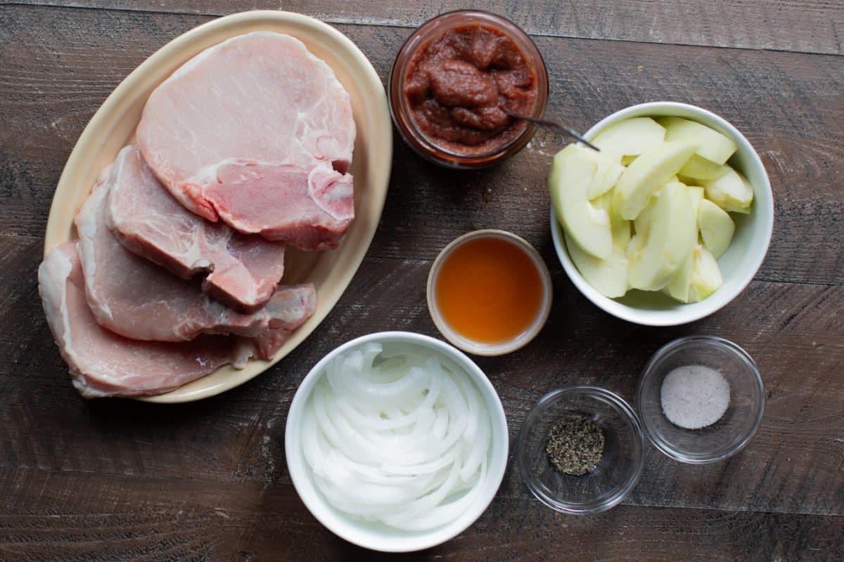 pork chops, apple cider vinegar, salt, pepper, apples, apple butter and onions in dishes.